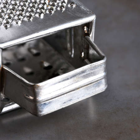 Closeup of a metal cheese grater on a baking sheet. Banco de Imagens