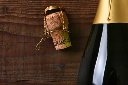 Overhead view of a Champagne bottle next to a cork and cage. Horizontal format on a dark wood background, with copy space.