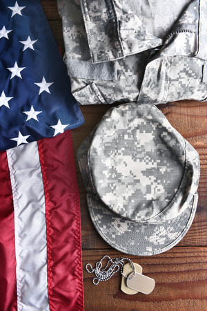 fatigues: Top view of military fatigues, dog tags and American Flag on a wood background. Military service concept for Memorial Day, Veterans Day and Patriotic events.