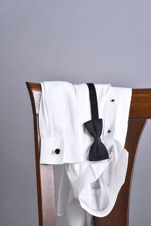 draped: Closeup of a tuxedo shirt draped over a chair back with a black bow tie. Vertical format with copy space. Stock Photo