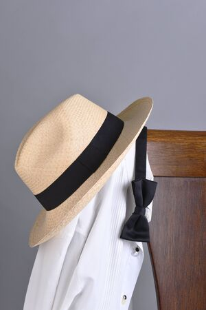 Closeup of a hat and tuxedo shirt hung on a chair back with a black bow tie. Vertical format with copy space.