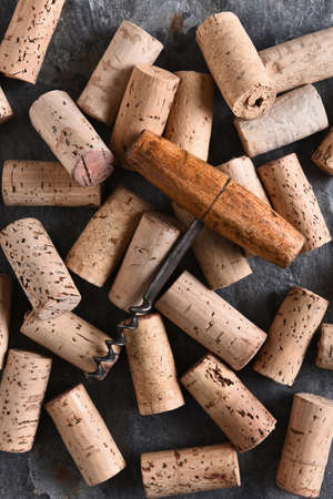 vertical format: An antique corkscrew laying on a group of corks. Vertical format shot from a high angle.