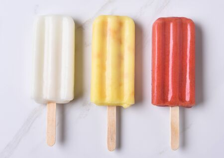 counter top: top view of three different ice pops on a marble counter top. Red, yellow and white fruit flavored pops.