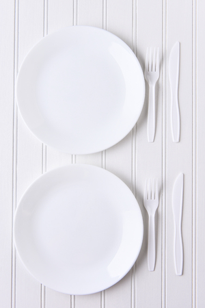 place setting: Top view of an all white place setting. White plates and plastic utensils on a white background. Stock Photo