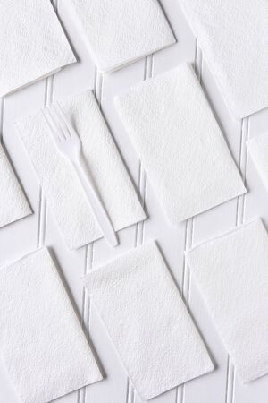 high angle: White Napkins on a White Table. A single plastic fork on one napkin. Vertical format from a high angle.