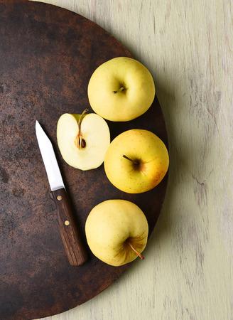 manzana verde: manzana Golden Delicious naturaleza muerta con el cuchillo. superficie redonda oscura en la mesa rústica.