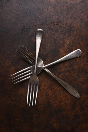 vertical format: Top view of a group of old forks on a dark mottled surface. Vertical format.