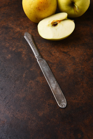paring: Closeup of an old knife with golden delicious apples in the background. Vertical format on a dark mottled surface.