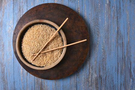 chop sticks: Brown Rice and Chop Sticks on a rustic blue wood table. Top view with copy space. Stock Photo