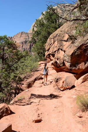 Woman hiking on the Grotto Trail in Zion National Park, Utah.