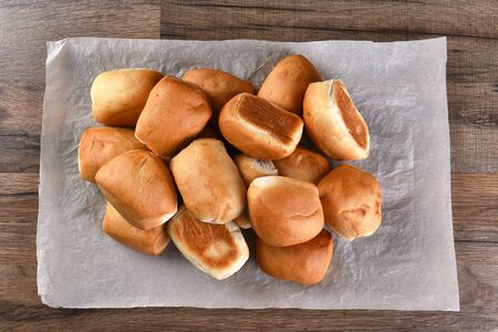 sheet pile: Pile of fresh baked dinner rolls on a sheet of parchment paper. Top view in horizontal format.