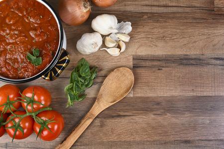 Bovenaanzicht van ingrediënten voor het maken van tomatensaus. Horizontaal formaat met kopie ruimte.