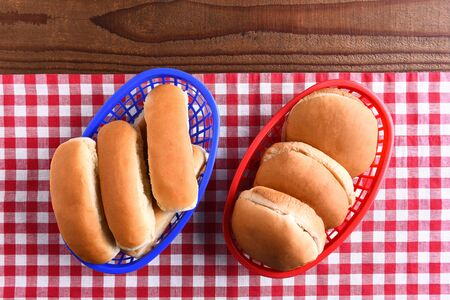 bollos: Hamburger and hot dog buns in plastic baskets on a picnic table . the red white and blue themed image is fit for patriotic holiday themes. Foto de archivo