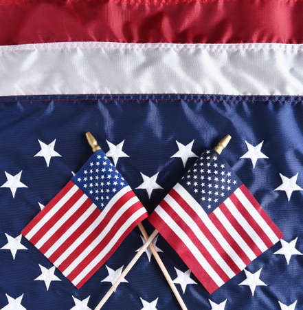banderas americanas: Two small American Flags on a larger Flag. Top view in square format.