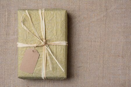 raffia: Christmas present wrapped with gold tissue paper, tied with raffia and a blank gift tag. On burlap with copy space.