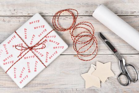 stamped: Christmas present stamped with the word Merry. High angle shot with scissors, twine and roll of wrapping paper.