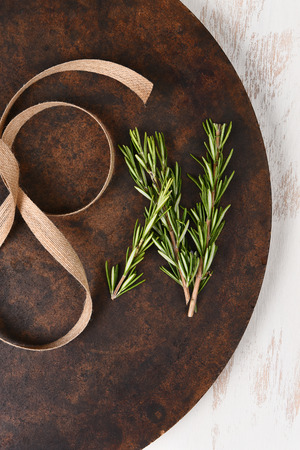 table surface: Rosemary and burlap ribbon on a round  flat stone surface on rustic wood table. Stock Photo