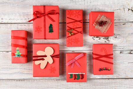 high angle view: High angle view of a variety of red wrapped Christmas presents on a rustiw white wood surface. Stock Photo