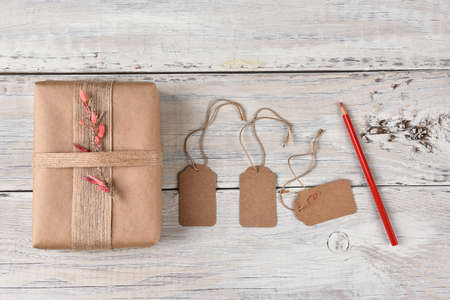 sackcloth: Top view of a Christmas present wrapped with brown paper, burlap ribbon and flowers next to gift tags and a red pencil.