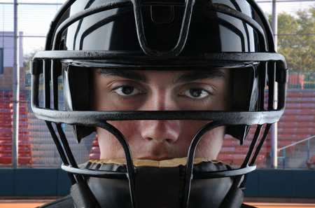 backstop: Closeup of a youth baseball catcher with backstop and grandstand in the background.