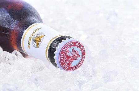 bottleneck: IRVINE, CA - JANUARY 11, 2015: Closeup of a single bottle of Singha Beer on ice. Produced by Boon Rawd Brewery it is the only brewery permitted to display the royal Garuda on the bottleneck.