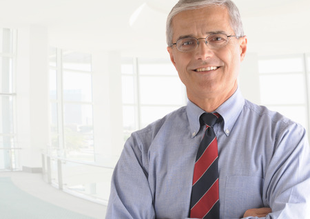 Business man portrait in high key office setting. Middle aged man is smiling at the camera and has his arms folded. Closeup head and shoulders only.