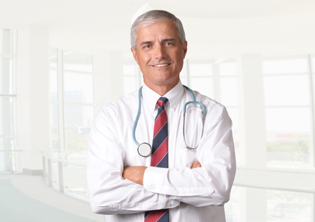 50 yrs: Smiling male doctor in scrubs with a stethoscope around his neck and his arms crossed. Vertical format torso view with high key background. Stock Photo