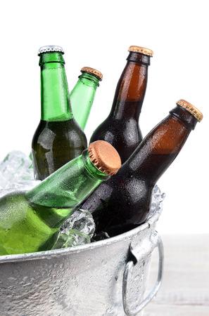 Closeup of green and brown beer bottles in a metal ice bucket.