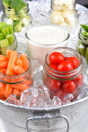 galvanized: Fresh vegetables in canning jars an ice bucket for a healthy picnic snack. Closeup in vertical format. Stock Photo