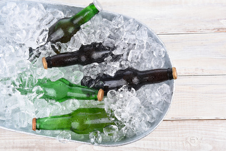 beer bucket: High angle view of a beer bucket filled with ice and assorted beer bottles. Horizontal format with copy space. Stock Photo