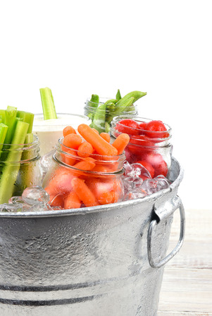 Closeup of fresh vegetables in a metal ice bucket on a rustic wood table, Isolated on white. Stock Photo