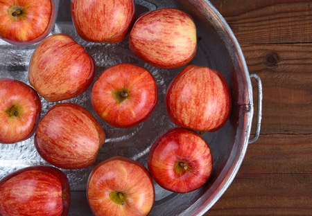 High angle closeup of a metal tub filled with water and apples for the Halloween custom of Apple Bobbing. Stok Fotoğraf