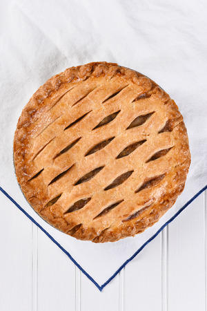pastry crust: High angle view of a fresh baked apple pie on a white kitchen towel, Vertical format.