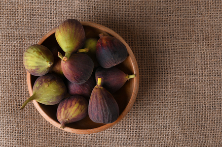 picked: A wood bowl full of fresh picked figs. horizontal format with copy space. Stock Photo