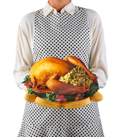 homemaker: Closeup of a homemaker in an apron and oven mitts holding a platter with a roasted turkey.  Woman is unrecognizable. Shallow depth of field over white..