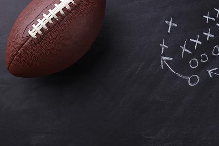 Vista dall'alto di un football in stile americano su una lavagna con un gioco nel diagramma. Formato orizzontale con copia spazio. Archivio Fotografico - 64002801