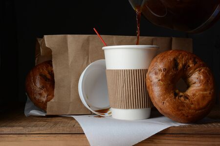 togo: A disposable cup of coffee and bag of bagels. A to-go breakfast meal  Stock Photo