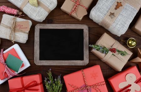 sackcloth: A group of Christmas presents on a dark wood table surrounding a blank chalkboard.