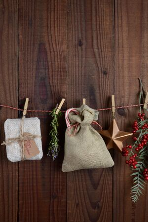 homey: Christmas gifts and decorations hanging from twine against a dar rustic wood wall. Vertical format with copy space.