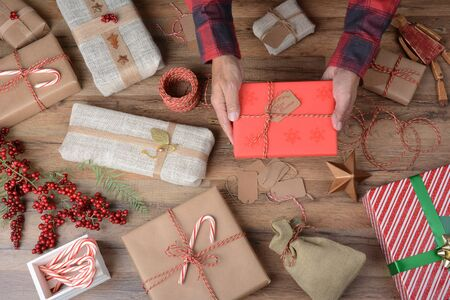 homey: High angle shot of a man holding a Christmas Present over a table filled with wrapped gifts and wrapping supplies. Stock Photo