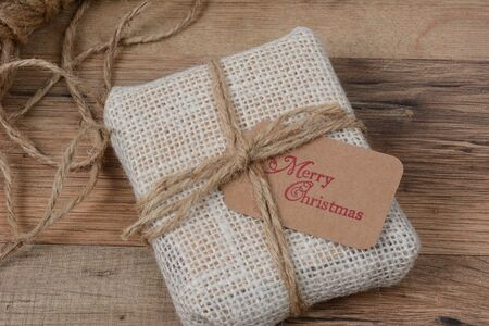 homey: Closeup of a small fabric present with a Merry Christmas gift tag on a wood table.