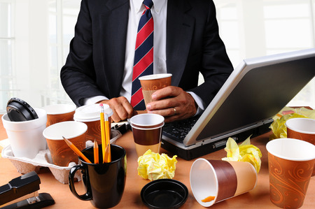 mess: Closeup view of a very cluttered businessmans desk. Man is holding a coffee cup and crumpled papers litter his workspace. HIgh Key Office Background. Stock Photo