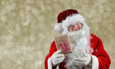 st  nick: Santa Claus holding a plain brown wrapped package. The eco friendly recyclable gift is tied with string and has a blank gift tag. On a light gold bokeh background.
