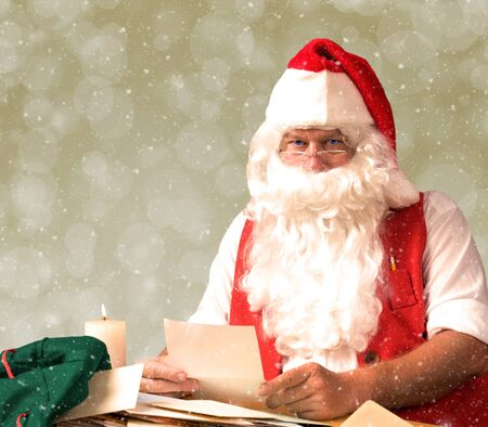 Santa Claus reading a letter by candle light with gold bokeh background and snow.