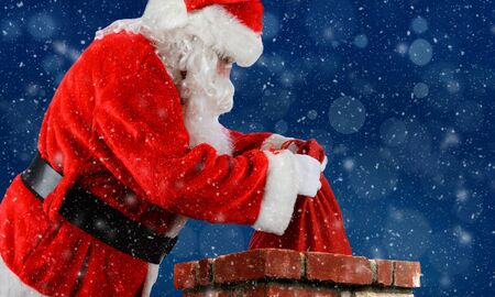 Closeup of Santa Claus placing his bag of toys into a chimney with snow flakes blue Bokeh background.