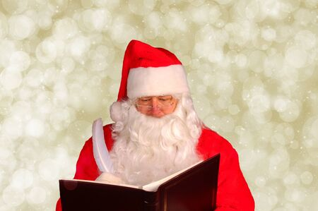 Closeup of Santa Claus writing in his Naughty and Nice Book. Horizontal format with gold bokeh background Stock Photo