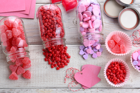 hearts: High angle view of different Valentines Day Candies on a rustic white wood table. Canning jars on their sides with candy spilling out.