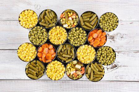 ejotes: Alto ángulo de disparo de un grupo de conservas vegetales sobre una mesa rústica de madera blanca. Varias variedades de las latas abiertas incluyendo, maíz, judías verdes, guisantes, zanahorias y verduras mixtas. Foto de archivo