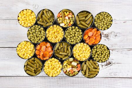 canned peas: High angle shot of a group of canned vegetables on a rustic white wood table. Several varieties of opened cans including, corn, green beans, peas, carrots and mixed veggies. Stock Photo