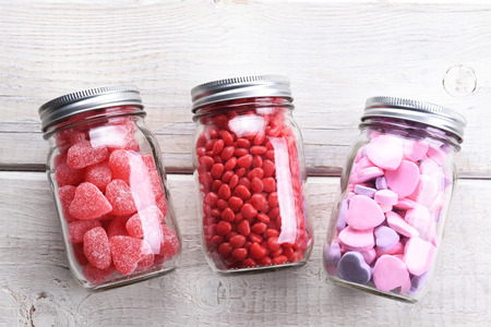 Canning jars laying on their sides filled with candy hearts and for Valentine's Day  on a rustic wood table. Imagens